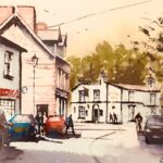 Village street scene looking towards a white pub, buildings on the left are also white and there are cars parked on either side of the street. Trees visible behind the pub & the sky is a beige colour