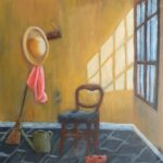 A corner of a room with yellow walls and grey floor tiles. Bright light is coming in from a large window on the right-hand side wall. Objects in the room include a dining chair upholstered in blue, pegs with a straw hat and pink fabric hanging, a broom, a watering can and some red shoes,