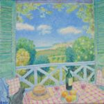 view from a French country balcony over fields, table and chairs with red and white check tablecoth with oranges and red wine