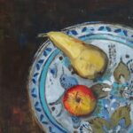 birds-eye view of an apple and pear sitting on a blue-and-white patterned plate on a dark brown surface.