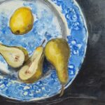 Birds-eye view of a cut pear, whole pear and lemon on a blue patterned plate on a dark grey surface.