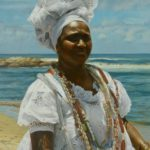 Portrait of a woman on a beach in white headdress and dress with necklaces