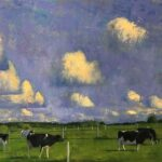 Fields with cows grazing in foreground, sky is mostly blue with a few individual white clouds.