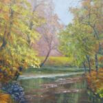 A river passing through trees, trees bending across river have golden-brown leaves.