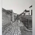 black-and-white drawing of an alley between houses, cobblestone path, walls along left hand side and fence along right, you can see more houses too.