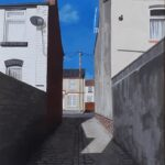 Looking down an alley between houses which is in shadow towards a house you can see the corner of, plus a telegraph pole, house behind that and blue sky