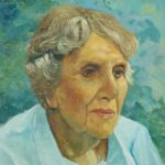 Portrait of a woman with short grey hair in a light blue shirt