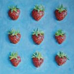bright blue background with nine strawberries set out in a 3 by 3 grid taking up most of the canvas