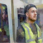 Man in high-vis vest on public transport