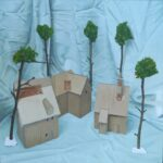 painting of three cardboard houses and 5 artificial trees, secured by gum or tack, all set on a blue cloth which folds into the backdrop