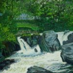 small waterfall in river by green fields