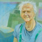 portrait of a man with white hair in a blue tshirt