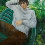 young man with dark hair, glasses and a grey jumper, sitting in relaxed pose on green garden chair