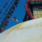 top of a stupa with prayer flags & an eye painted