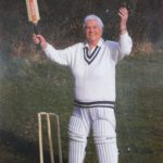 man in cricket whites with bat, raising arms & smiling, next to stumps