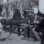 two people sitting on a bench playing accordions wearing horse head masks. A child is watching