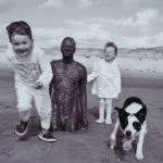 two young children & a dog by half-buried Iron Man statue at Crosby beach. Black & white