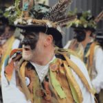 man dressed for morris dancing, black face paint around eyes