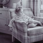 very young child sitting plaid print chair looking out the window