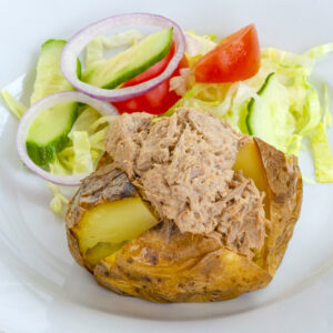 Photograph of a tuna-filled jacket potato on a white plate accompanied by some salad