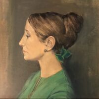 side profile of woman in green with hair up