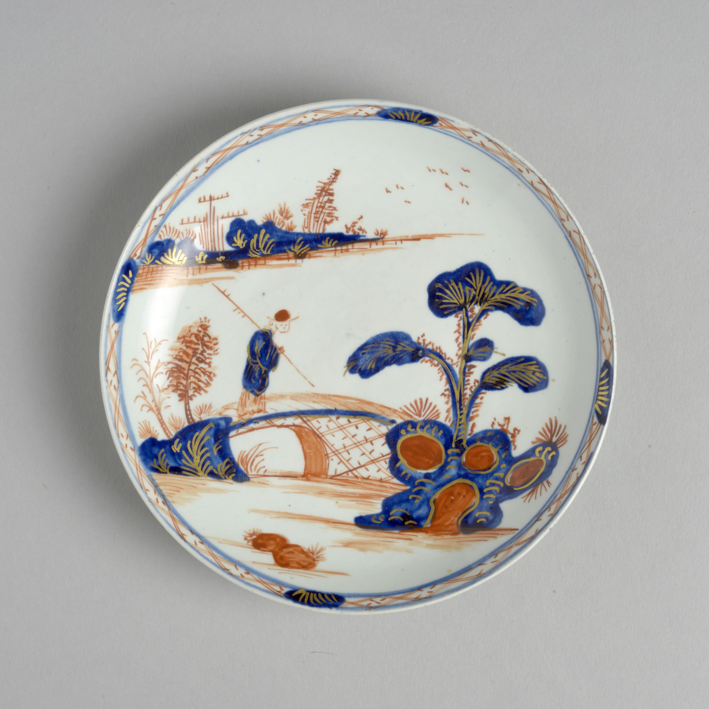A white saucer decorated with a design which is clearly inspired by willow pattern - a man crossing a chinese bridge - but in orange as well as blue.