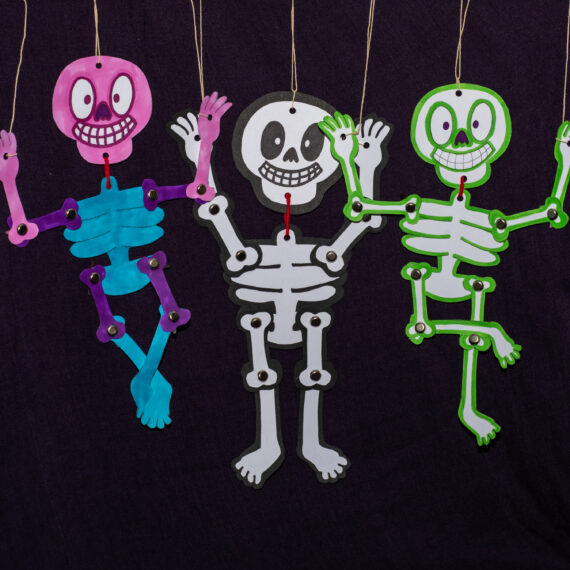 Three paper skeleton puppets. One on the left is pink and blue, the centre is white and the right is green and white.