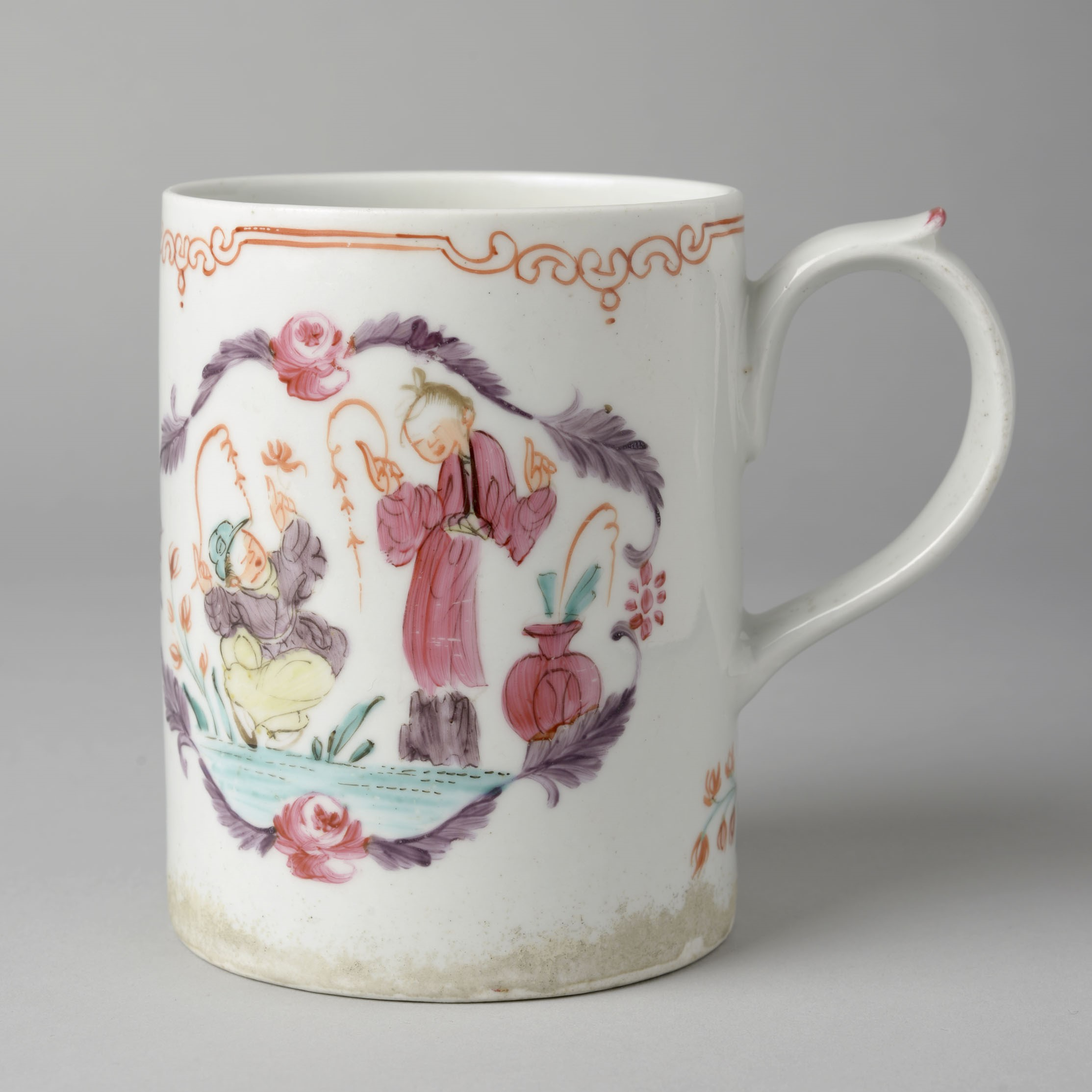 A white porcelain cup decorated with a cameo featuring two men; however it's unclear what they're doing as the cup is turned to the side.