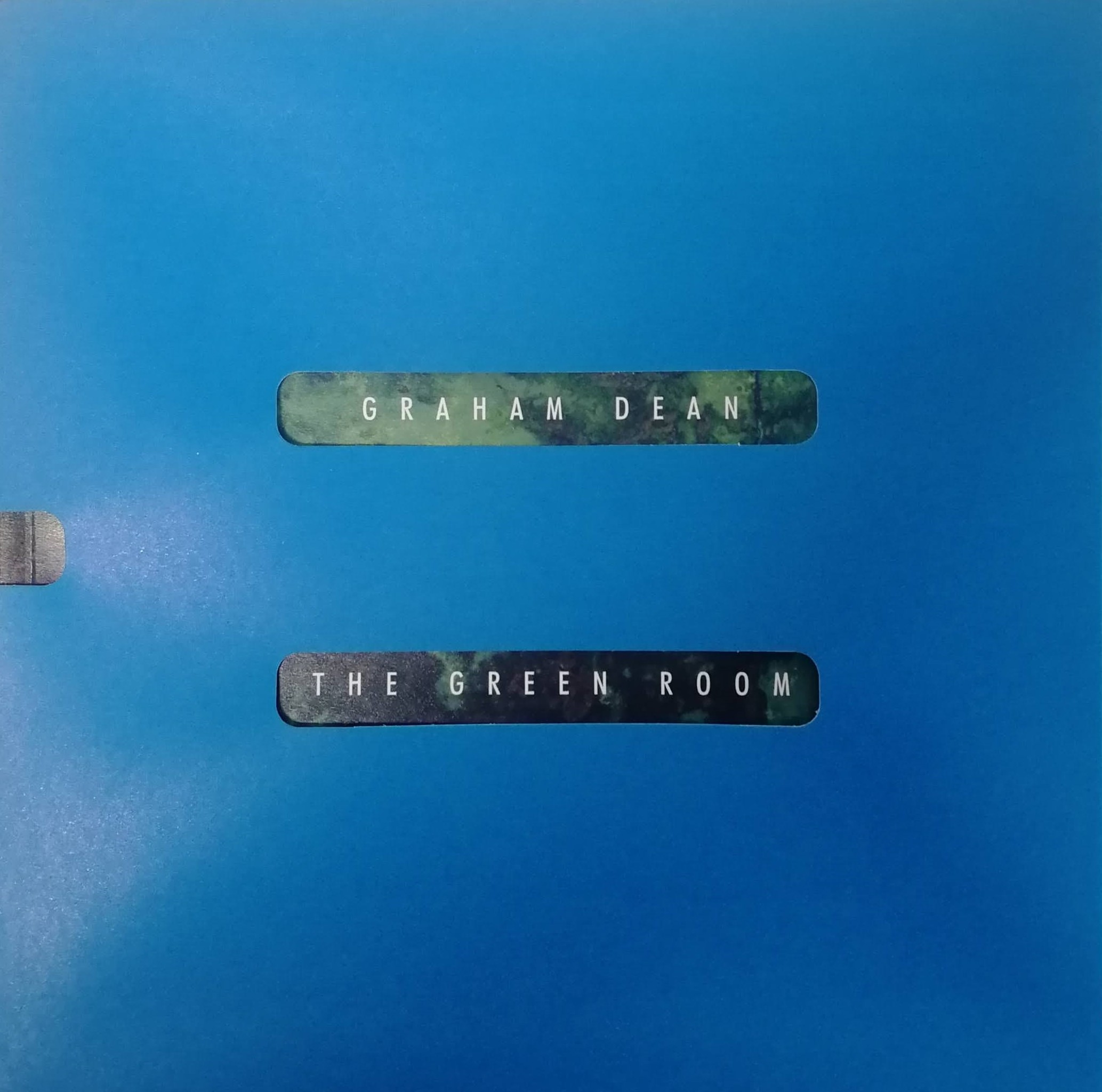 """Image of an exhibition catalogue in a blue sleeve. There are two holes in the blue where we can see a green background and the words """"Graham Dean"""" and """"The Green Room""""."""