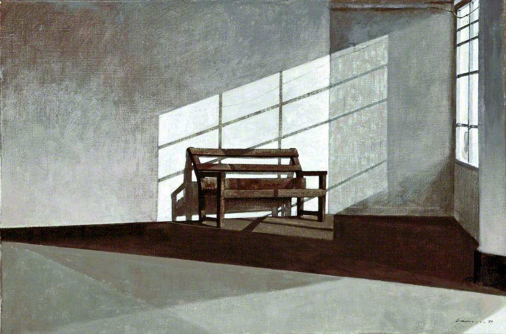 grey walled room with a single bench, light coming in from window onto the bench.