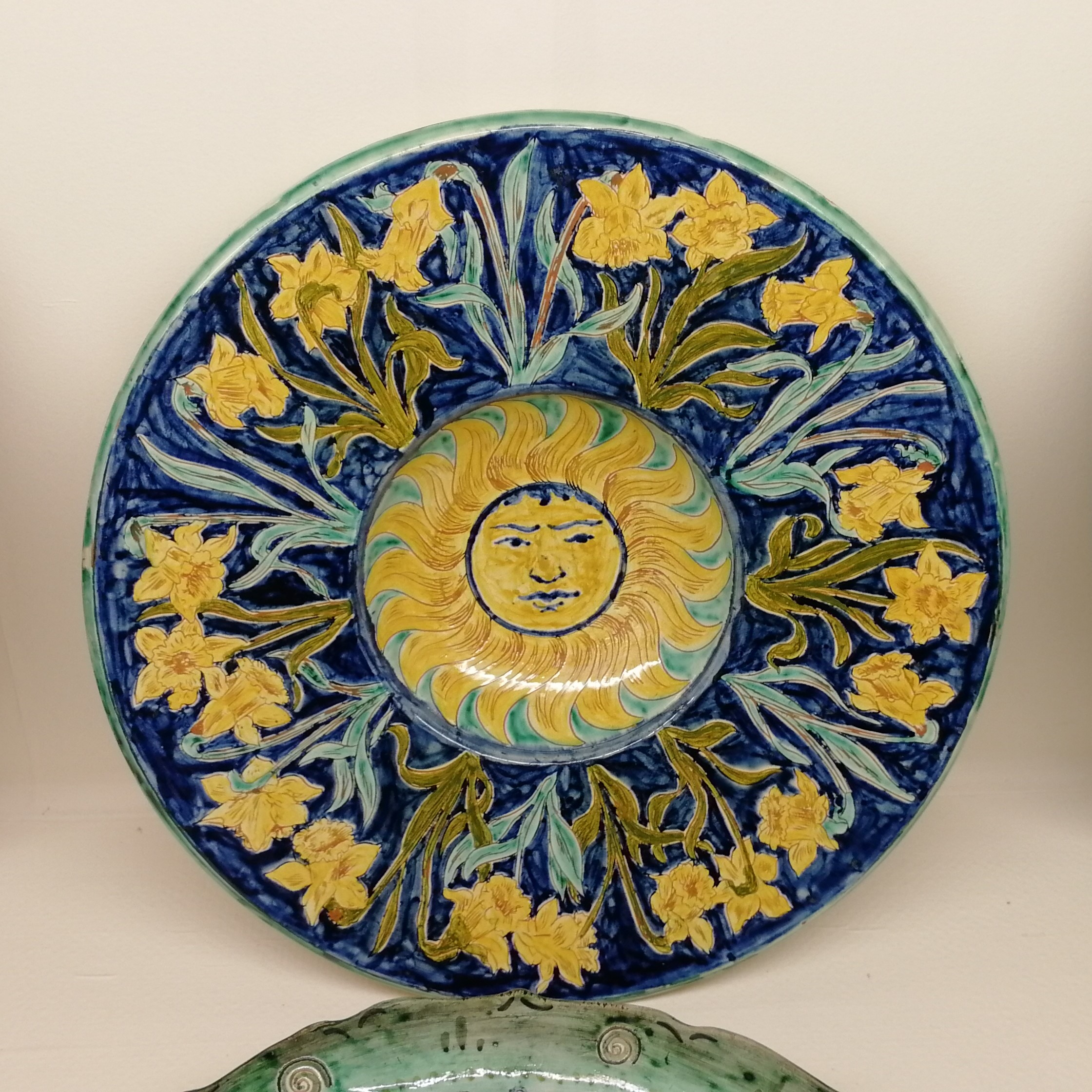 a decorative plate. In the centre is a bright yellow sun with a human face. Around the outside of this is a dark blue background decorated with yellow and green daffodils